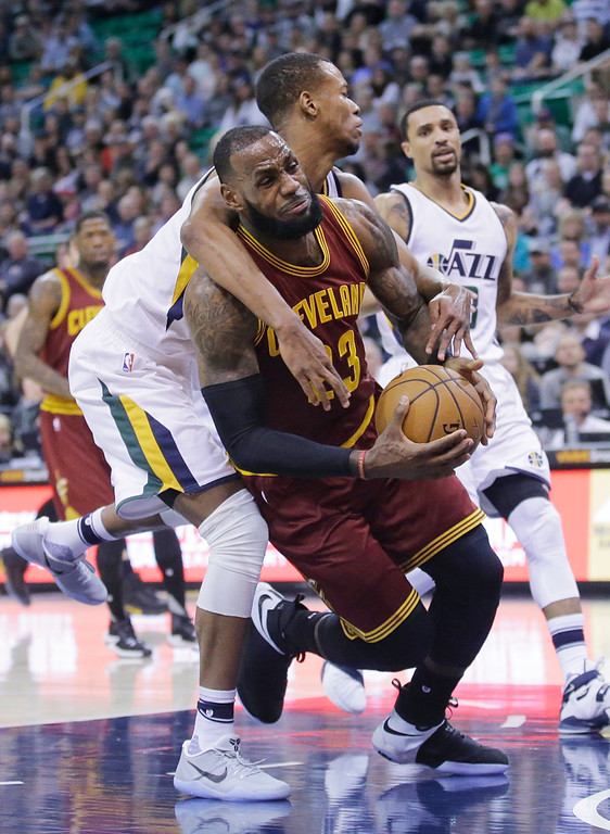 . Utah Jazz guard Rodney Hood, rear, fouls Cleveland Cavaliers forward LeBron James (23) as he goes to the basket in the first half during an NBA basketball game Tuesday, Jan. 10, 2017, in Salt Lake City. (AP Photo/Rick Bowmer)