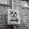 Radiation hazard sign pasted on a one way sign, brick wall, Seattle, Washington, 1992, Ilford HP5 plus.