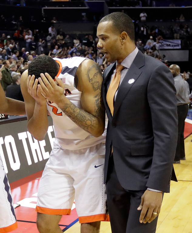 . Virginia\'s Isaiah Wilkins, left, walks off the court after the team\'s 74-54 loss to UMBC in a first-round game in the NCAA men\'s college basketball tournament in Charlotte, N.C., Friday, March 16, 2018. (AP Photo/Gerry Broome)