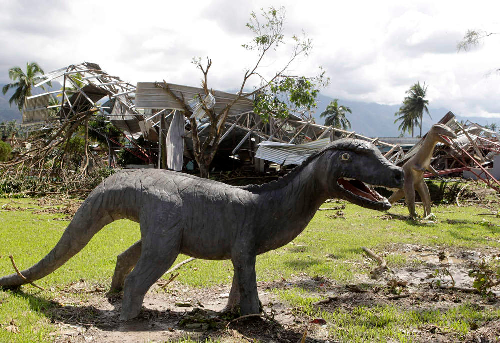 Description of . Concrete-made dinosaurs statues stand next to a collapsed building destroyed by Typhoon Bopha at a playground in New Bataan town in Compostela Valley, southern Philippines December 8, 2012. Philippine President Benigno Aquino declared a state of national calamity on Saturday, four days after this year\'s strongest typhoon left nearly 1,000 people dead or missing mostly in the country\'s resource-rich south. REUTERS/Erik De Castro