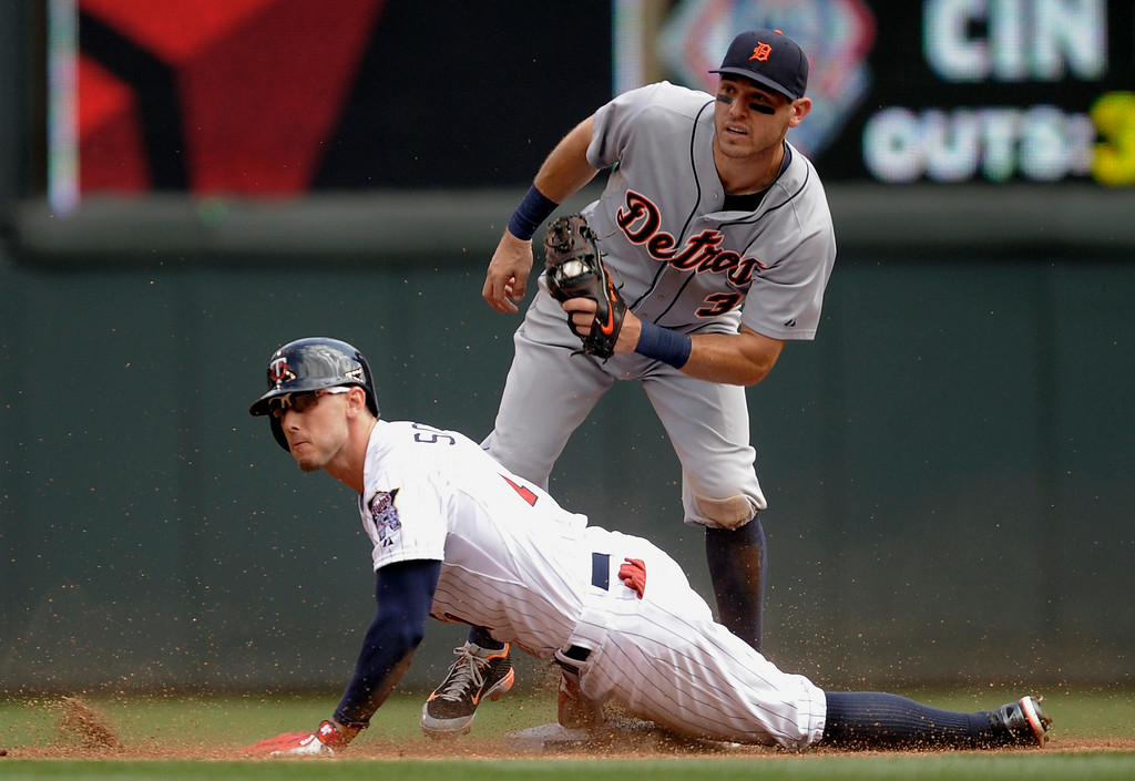 . Minnesota Twins\' Jordan Schafer, left, slides in with a double as Detroit Tigers second baseman Ian Kinsler, right, attempts the tag during the third inning of a baseball game in Minneapolis, Sunday, Aug. 24, 2014. (AP Photo/Tom Olmscheid)