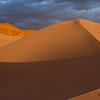 A hiker stands atop a sand dune ridge at Ibex Dunes in Death Valley National Park, California
