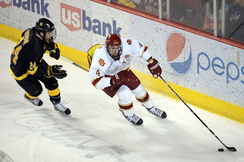 . DENVER, CO. - FEBRUARY 08: Joshiah Didier of University of Denver #4 tries to carry the puck past by Jared Hanson of Colorado College #24 February 8, 2013 at Magness Arena in Denver, Colorado. (Photo By Hyoung Chang/The Denver Post)