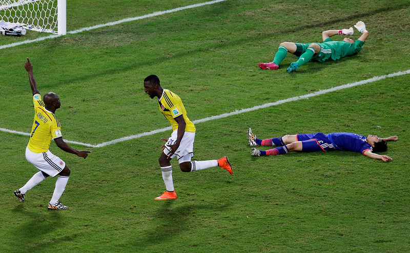 . Colombia forward Jackson Martinez, celebrates his goal with Pablo Armero, left, past Japan defender Atsuto Uchida and goalkeeper Eiji Kawashima during the second half of a group C World Cup soccer match at the Arena Pantanal in Cuiaba, Brazil, Tuesday, June 24, 2014. (AP Photo/Shuji Kajiyama)