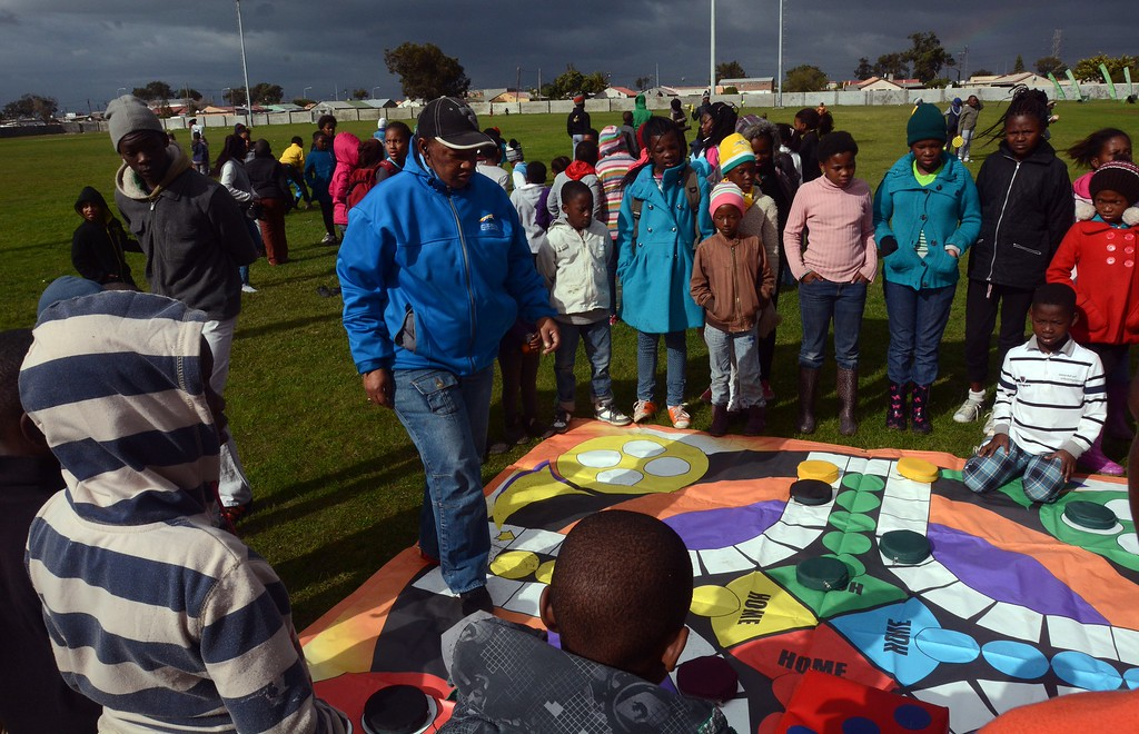 . A man helps children play  large boardgames on a field, as sports and fun events are available, as part of the South African Rugby Union\'s and the City of Cape Town\'s contribution to Mandela Day, on July 18, 2014, in Langa, an impoverished area about 20Km from the centre of Cape Town. Mandela Day, celebrated on Nelson Mandela\'s birthday inspires people to give 67 minutes of their time, helping those less fortunate. 