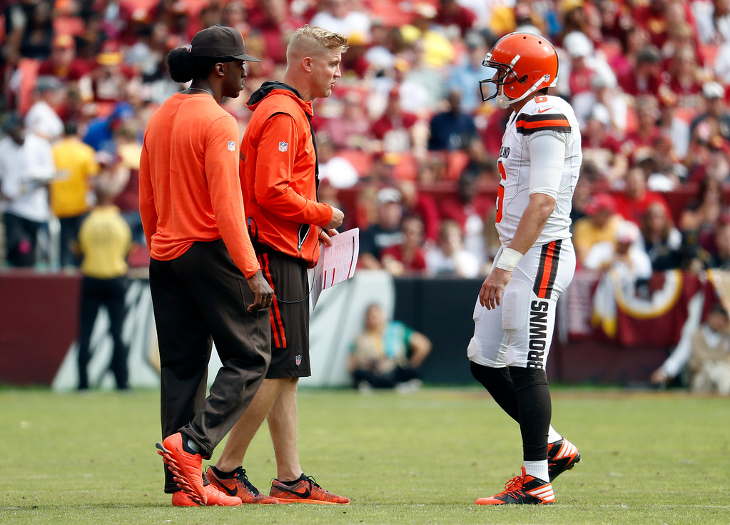 . Injured Cleveland Browns quarterbacks Robert Griffin III, left, and Josh McCown talk with quarterback Cody Kessler (6) during the first half of an NFL football game against the Washington Redskins, Sunday, Oct. 2, 2016, in Landover, Md. (AP Photo/Carolyn Kaster)