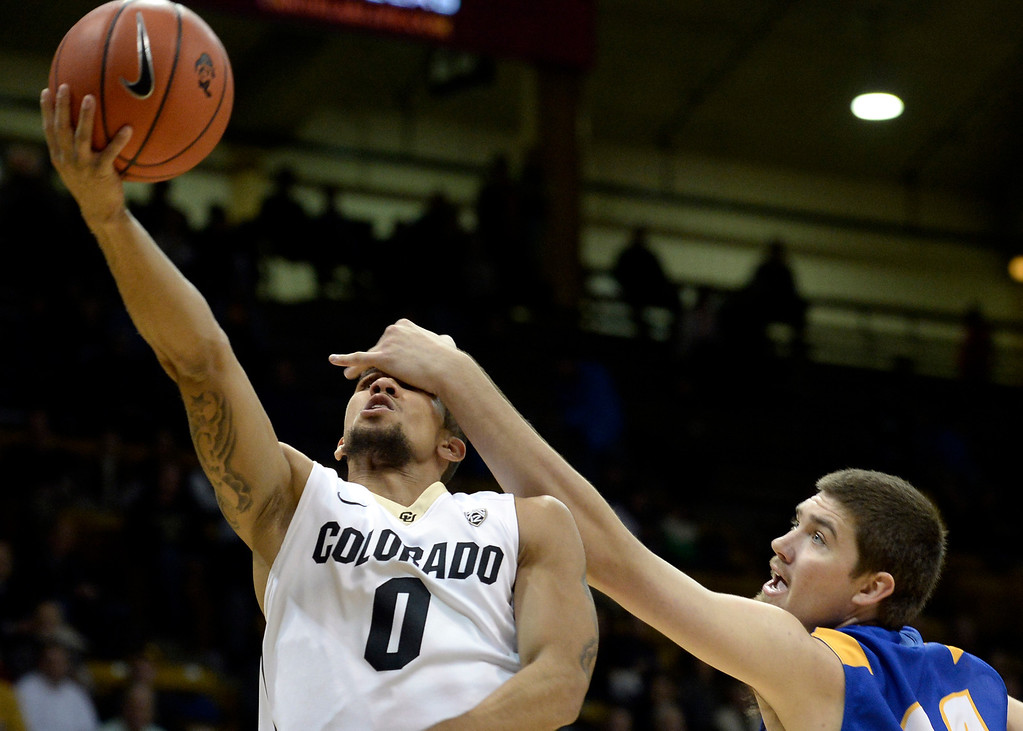 . University of Colorado\'s Askia Booker gets fouled by Sam Beeler while going for a layup during a game against  the University of California Santa Barbara, on Nov. 20, at the Coors Event Center in Boulder.  (Jeremy Papasso/Boulder Daily Camera)