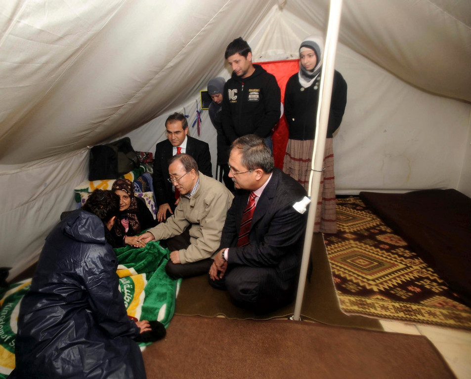 ". U.N. Secretary-General Ban Ki-moon (squatting C) chats with a Syrian refugee woman during his visit to a camp in the Turkish town of Islahiye, Gaziantep province December 7, 2012. Ban said on Friday he was not aware of any confirmed reports that Syrian President Bashar al-Assad was preparing to use chemical weapons but that if he did so it would be an ""outrageous crime\"". REUTERS/Veli Gurgah/Pool"