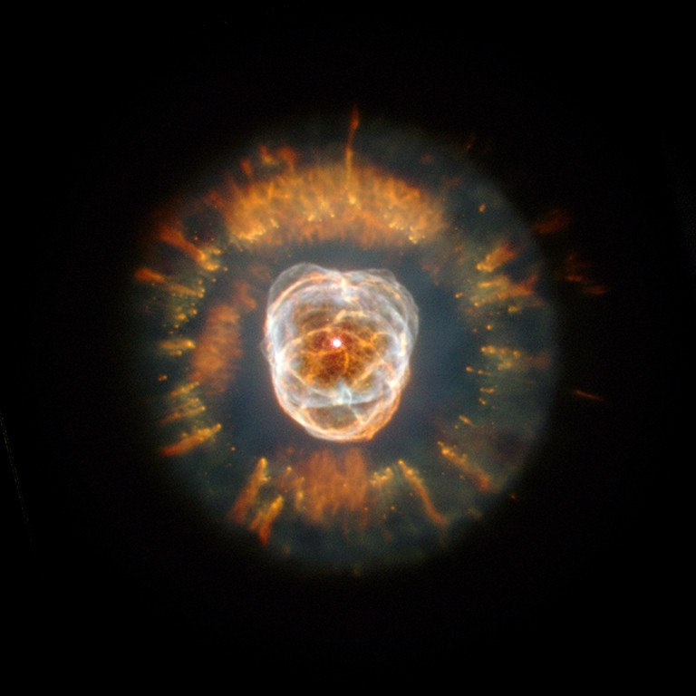 ". 2000: The Eskimo Nebula (NGC 2392)  In its first glimpse of the heavens following the successful December 1999 servicing mission, NASA\'s Hubble Space Telescope has captured a majestic view of a planetary nebula, the glowing remains of a dying, Sun-like star. This stellar relic, first spied by William Herschel in 1787, is nicknamed the ""Eskimo\"" Nebula (NGC 2392) because, when viewed through ground-based telescopes, it resembles a face surrounded by a fur parka. In this Hubble telescope image, the \""parka\"" is really a disk of material embellished with a ring of comet-shaped objects, with their tails streaming away from the central, dying star. The Eskimo\'s \""face\"" also contains some fascinating details. Although this bright central region resembles a ball of twine, it is, in reality, a bubble of material being blown into space by the central star\'s intense \""wind\"" of high-speed material. Credit: NASA, Andrew Fruchter and the ERO Team [Sylvia Baggett (STScI), Richard Hook (ST-ECF), Zoltan Levay (STScI)"