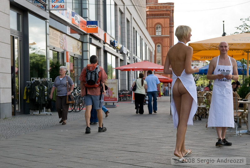 "Two persons wearing only shoes and apron are attracting passers-by promoting solvable bubble foam to save plastic and respect the environment; ""ask me why I'm naked"", the message is the content is the most important, not the packaging"