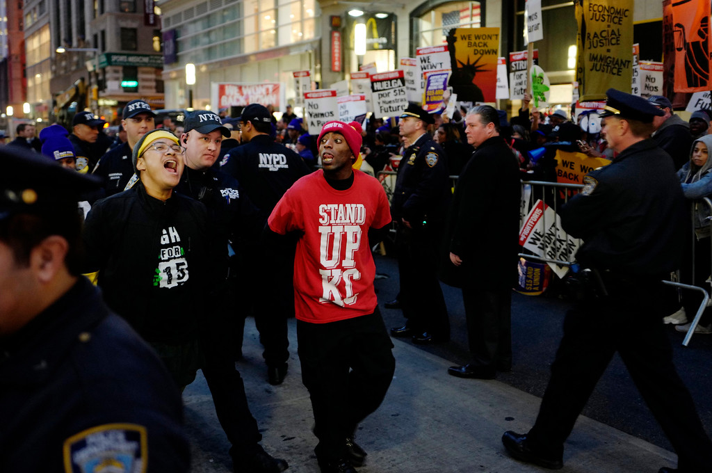 . Two men, center, are arrested by police officers after blocking Broadway in front of a McDonald\'s restaurant, Tuesday, Nov. 29, 2016, in New York. About 25 chanting minimum-wage protesters were arrested. They were among about 350 people at a peaceful rally Tuesday. The event was part of the National Day of Action to Fight for $15. The campaign seeks higher hourly wages, including for workers at fast-food restaurants and airports. (AP Photo/Mark Lennihan)