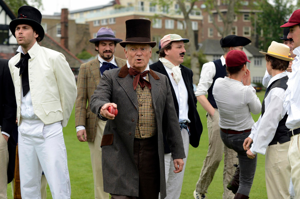 . Author Jeffrey Archer (C) gestures as he acts as an umpire during a Victorian Cricket match to commemorate the 150th anniversary of Wisden Cricketers\' Almanack  at Vincent Square in London May 29, 2013. REUTERS/Philip Brown