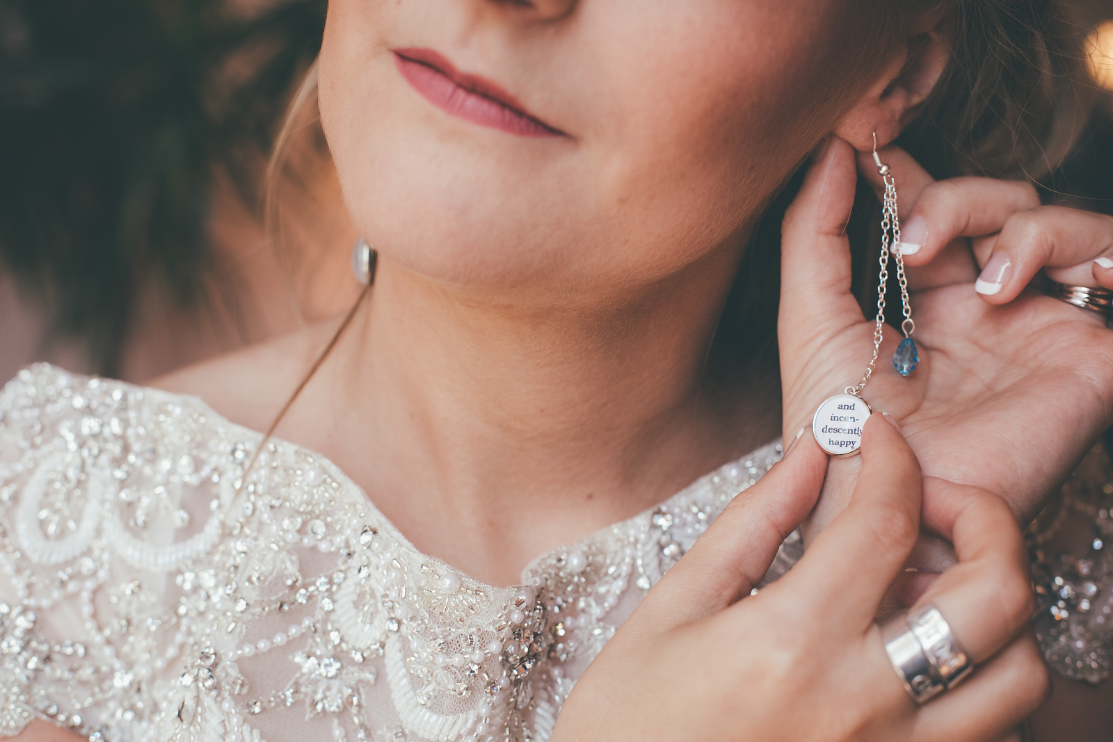 close up shot of a brides earring that reads and incandescently happy