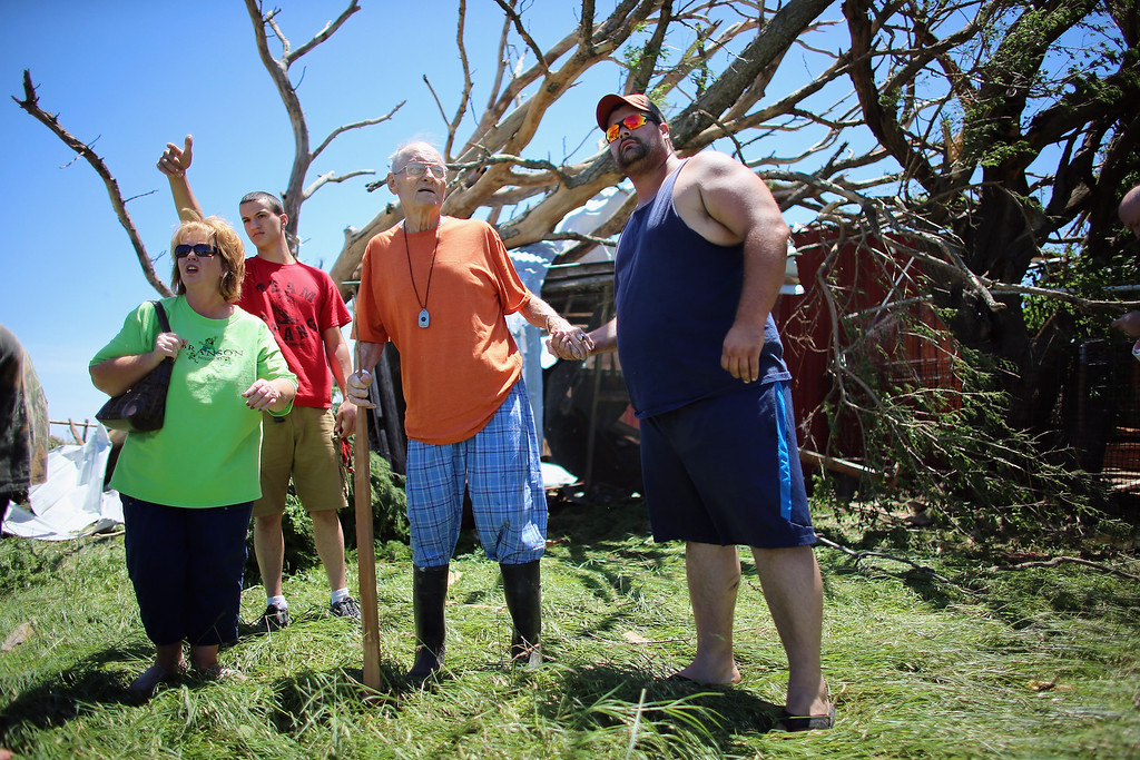 . EL RENO, OK - JUNE 01: Bill Thesing (2R), who was injured in his home when a tornado hit, returned to what was left of it from the hospital to look for some of his lost animals with (L-R) Tammy Hicks, Dylan Lager and Chad Beckman on June 1, 2013 in El Reno, Oklahoma. The tornado ripped through the area killing at least nine people, injuring many others and destroying homes and buildings.  (Photo by Joe Raedle/Getty Images)