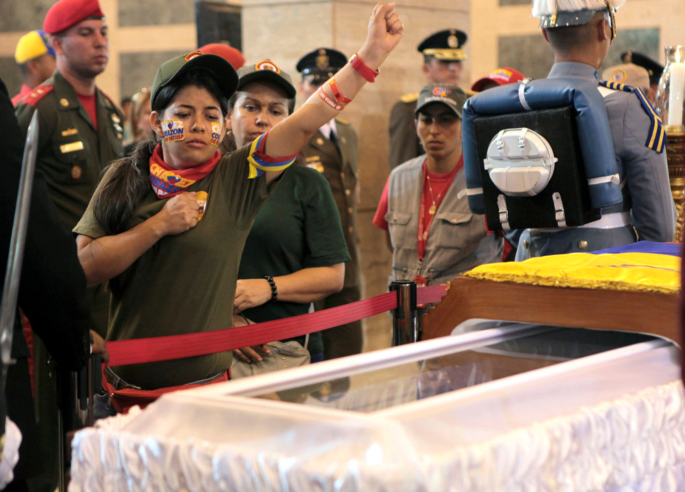 . A woman pays her respects as she files past the glass-topped casket containing the remains of Venezuela\'s late President Hugo Chavez lying in state at the military academy in Caracas, Thursday, March 7, 2013. Chavez died of a massive heart attack Tuesday after great suffering and inaudibly mouthed his desire to live, the head of Venezuela\'s presidential guard said late Wednesday. (AP Photo/Miraflores Presidential Press Office)