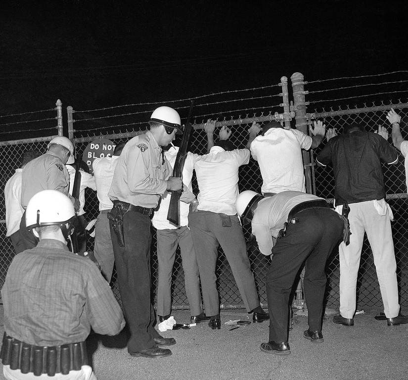 . Police search youths in riot area of Cleveland, July 23, 1966 as trouble continued for a fifth night with reports of shooting and minor incidents. (AP Photo/Charles Knoblock)