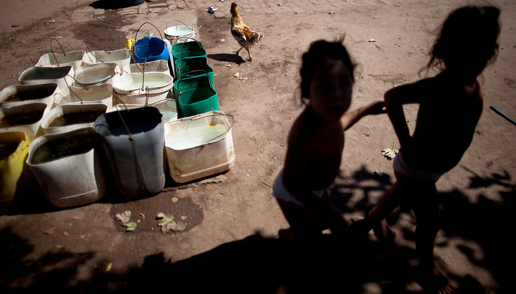 . Erika, left, and her twin sister Macarena, who suffer from chronic respiratory illness, play in their backyard near recycled agrochemical containers filled with water that is used for flushing their toilet, feeding their chickens and washing their clothes, near the town of Avia Terai, in Chaco province, Argentina on March 31, 2013. The twins\' mother, Claudia Sariski, whose home has no running water, says she doesn\'t let her children drink the water from the discarded pesticide containers. (AP Photo/Natacha Pisarenko)