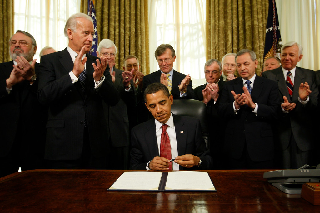 . President Barack Obama caps his pen after he signed an executive order closing the prison at Guantanamo Bay, Thursday, Jan. 22, 2009, in the Oval Office of the White House in Washington. Vice President Joe Biden, second from left, and retired military officers applaud. (AP Photo/Charles Dharapak)