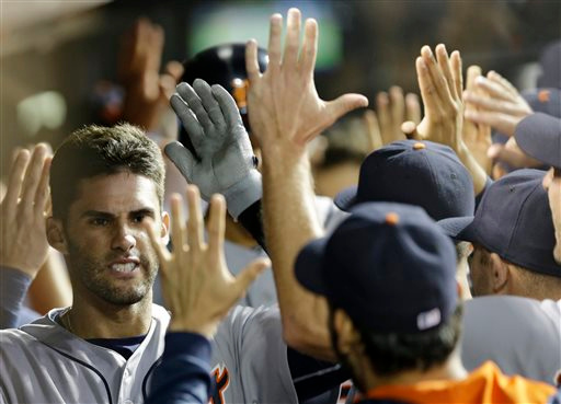 . Detroit Tigers\' J.D. Martinez, left, is congratulated in the dugout after hitting a three-run home run off Cleveland Indians relief pitcher Cody Allen in the ninth inning of a baseball game, Tuesday, Sept. 2, 2014, in Cleveland. Steven Moya and Torii Hunter scored on the play. The Tigers defeated the Indians 4-2. (AP Photo/Tony Dejak)