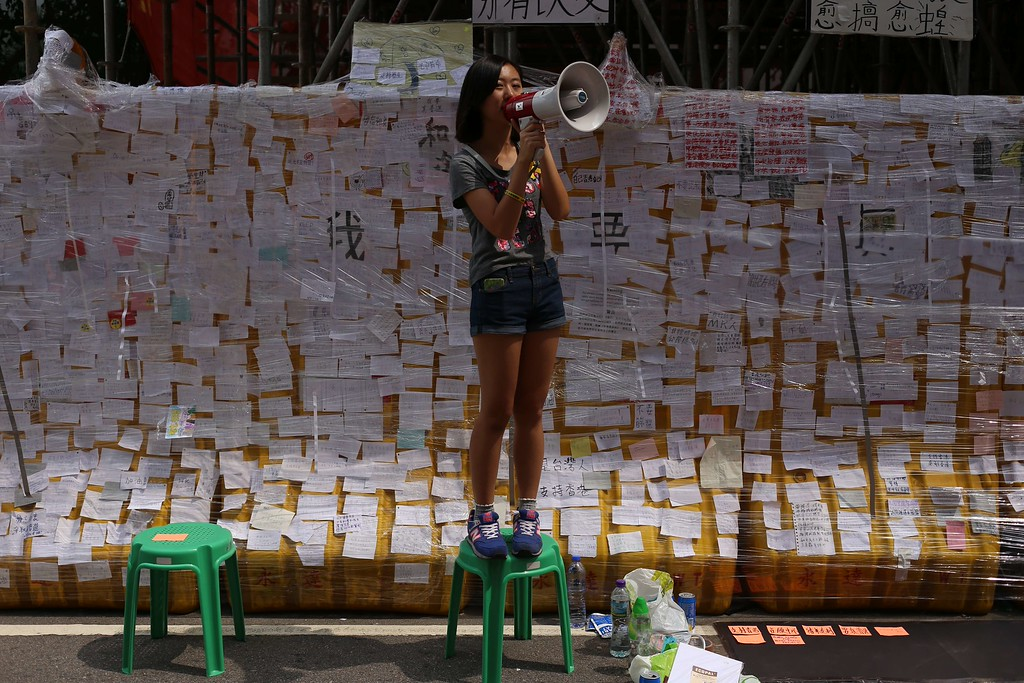 ". A student protester speaks into a microphone in front of a ""democracy wall\"" filled with notes supporting the pro-democracy protest in Hong Kong on October 2, 2014.  Tensions in Hong Kong soared after police were seen unloading boxes of tear gas and rubber bullets close to the city\'s besieged government headquarters as the authorities urged pro-democracy demonstrators to disperse \""as soon as possible\"".    AARON TAMaaron tam/AFP/Getty Images"