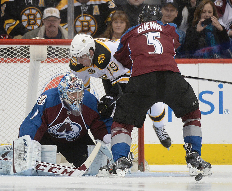 . Colorado defenseman Nate Guenin (5) challenged Boston wing Reilly Smith (18) in front of Colorado goaltender Semyon Varlamov (1) in the first period. The Colorado Avalanche hosted the Boston Bruins at the Pepsi Center Friday night, March 21, 2014. (Photo by Karl Gehring/The Denver Post)