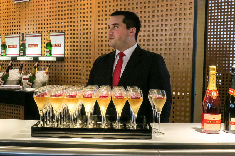 Man standing behind a tray of filled champagne glasses