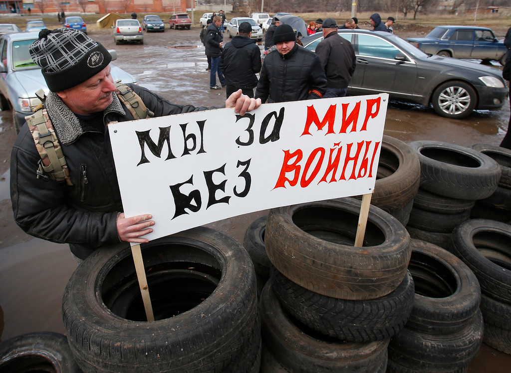". Pro Russian activists install a placard reading ""We are for peace without wars\""  in their camp near the armory of Ukrainian army in the village of Poraskoveyevka, eastern Ukraine, Thursday, March 20, 2014.  (AP Photo/Sergei Grits)"