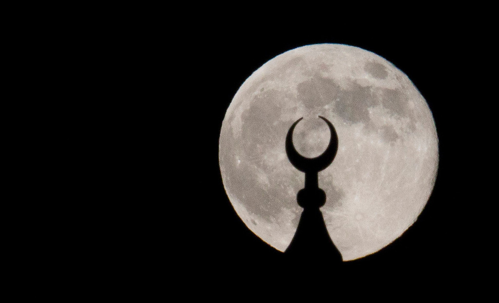 ". A ""super moon\"" rises behind the minaret of the Ahi Celebi Mosque in Istanbul, Turkey on Sunday, June 23, 2013. The moon, which will reach its full stage on Sunday, is expected to be 13.5 percent closer to earth during a phenomenon known as a \""super moon\"". The \""super moon\"" happens only once this year as the moon on its elliptical orbit is at its closest point to earth.  (AP Photo/Gero Breloer)"