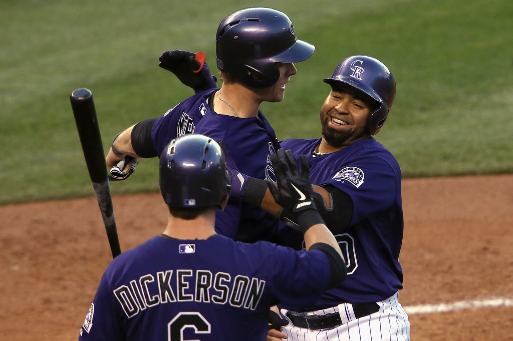 . Wilin Rosario #20 of the Colorado Rockies celebrates his three run home run off of starting pitcher Ryan Vogelsong #32 of the San Francisco Giants with Justin Morneau #33 and Corey Dickerson #6 of the Colorado Rockies as the Rockies took a 4-0 lead in the first inning at Coors Field on April 21, 2014 in Denver, Colorado.  (Photo by Doug Pensinger/Getty Images)