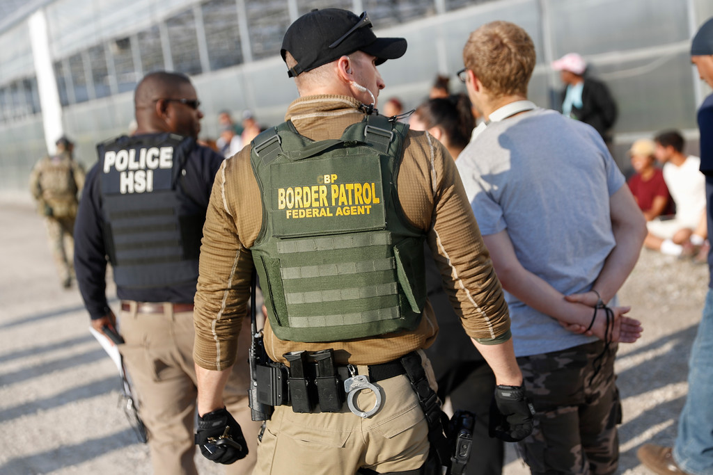 . Government agents lead suspects in custody during an immigration sting at Corso\'s Flower and Garden Center, Tuesday, June 5, 2018, in Castalia, Ohio. The operation is one of the largest against employers in recent years on allegations of violating immigration laws. (AP Photo/John Minchillo)