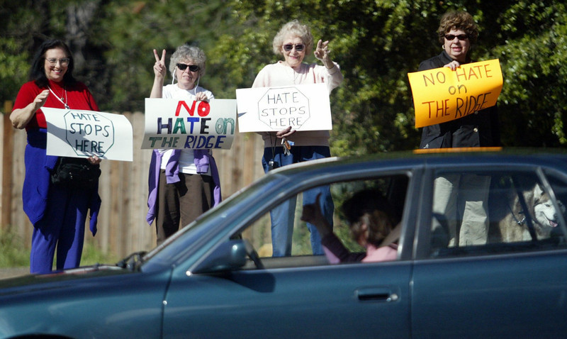 "From left to right, Sandy Abrams, Mary Shallenberger, Peggy Eaton, and Lara Gularte wave to a supportive motorist who gives a thumbs up as she drives by the corner of Skyway and Coutolenc Thursday afternoon, where about 40 people gathered to rally for anti-hate after a fence was grafittied ""Keep Magalia White"" with a swastika above it."