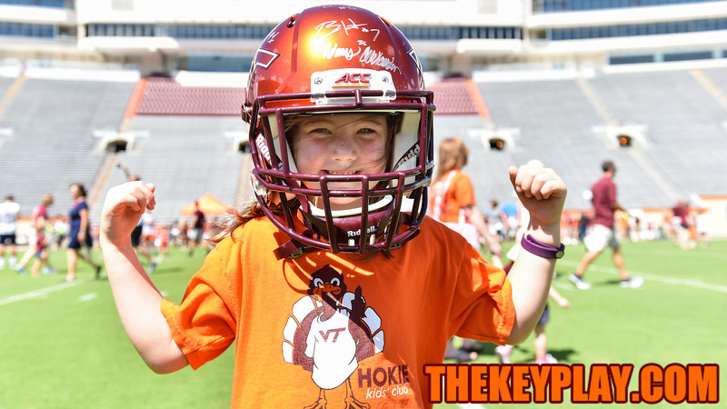 A young Hokie fan flexes while wearing her helmet signed by many players. (Michael Shroyer/ TheKeyPlay.com)