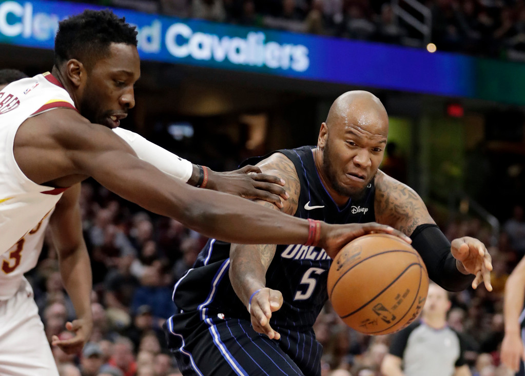 . Cleveland Cavaliers\' Jeff Green, left, and Orlando Magic\'s Marreese Speights reach for a loose ball during the first half of an NBA basketball game Thursday, Jan. 18, 2018, in Cleveland. (AP Photo/Tony Dejak)