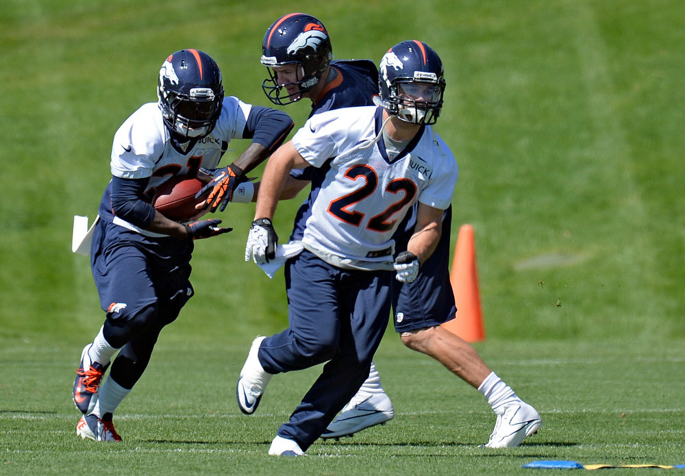 . Quarterback Peyton Manning (18) hands off to Ronnie Hillman (21) as he follows Jacob Hester (22) during OTAs June 6, 2013 at Dove Valley. (Photo By John Leyba/The Denver Post)