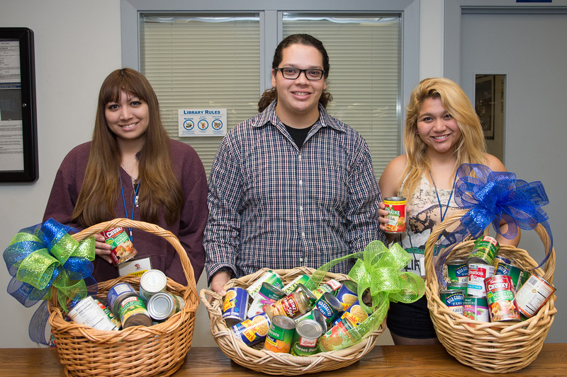Students Lauren Alejauh(left), Joe Hernandez and Carlas Bias shows 273 cans (300lb) collected from Fine Amnesty Food Drive at Mary and Jeff Bell Library.