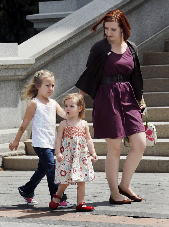 . Six-year-old transgender girl Coy Mathis, left, her sister Auri and mother Kathryn Mathis walk to a news conference at the Capitol in Denver on Monday, June 24, 2013. The Colorado Civil Rights Division has ruled in favor of six-year-old Coy Mathis, whose school had barred her from using the girls\' bathroom at her elementary school because she is transgender.  (AP Photo/Ed Andrieski)