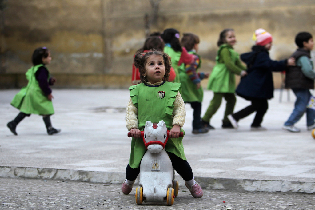 . A girl looks up to the sky after hearing the sound of shelling as she sits on a toy pony in the playground of Al-Tawheed school in Aleppo January 1, 2013. REUTERS/Muzaffar Salman