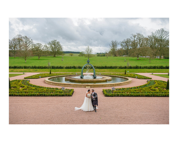 Wedding Photography of Louise & Jason, Dunfries House, Scotland, Photograph is of the Bride & Groom standing with the famous fountain and the grounds of the house behind them