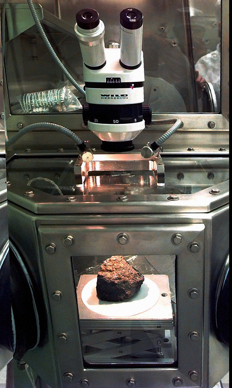 . The meteorite labeled ALH84001 sits under a microscope at a Johnson Space Center lab in Houston,in this Aug. 7, 1996 file photo. Researchers at NASA and three universities claimed to have found in the rock from Mars organic compounds they said were deposited by primitive life forms before the meteorite was blasted into space and sent on a 15 million-year voyage to Earth. (AP Photo/David J. Phillip)