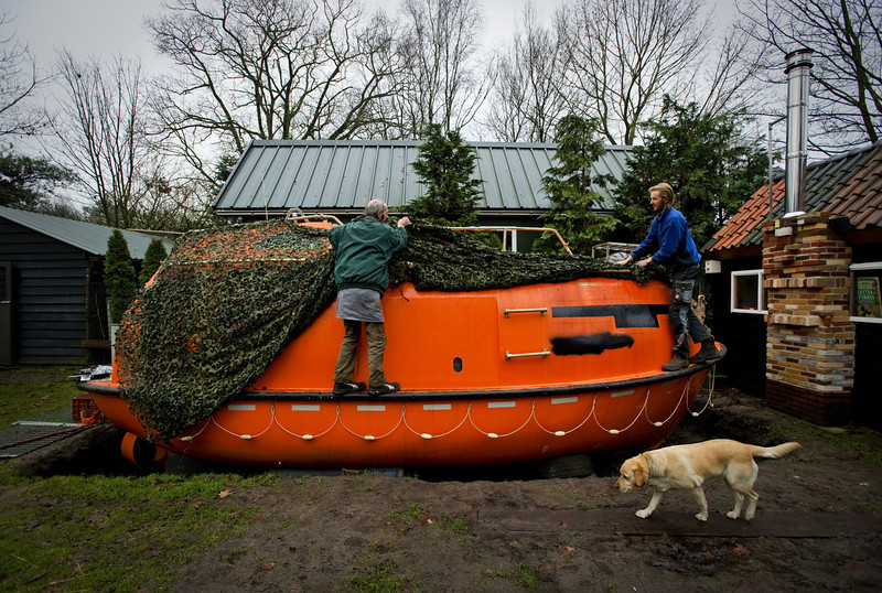". Duch Pieter van der Meer (L) and a friend uncover on December 19, 2012 his Norwegian lifeboat in his garden in Kootwijkerbroek with which he can save 35 persons in case of a global apocalypse hits on 21 December. The date marks the end of an era that lasted over 5,000 years, according to the Mayan ""Long Count\"" calendar. Some believe that the date, which coincides with the December solstice, marks the end of the world as foretold by Mayan hieroglyphs -- an idea ridiculed by scholars. AFP PHOTO / ANP / ROBIN VAN LONKHUIJSEN"