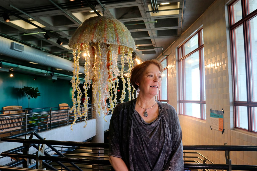 . In this photo taken July 26, 2018, Angela Haseltine Pozzi, of Bandon, Ore., describes her project Washed Ashore: Art to Save the Sea at the Audubon Aquarium of the Americas in New Orleans as she stands in front of a giant jellyfish sculpture made from fishing buoys and cut-up water bottles that washed up on the Pacific Coast. (AP Photo/Janet McConnaughey)