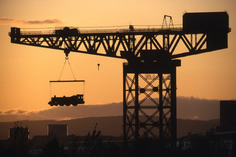 Not quite what it seems - the locomotive suspended from the Finnieston Crane was fashioned from straw by the wonderful George Wylie (the scul?tor), and hung there for the duration of the Garden Festival. It was later ceremonially burnt (though not in situ - which would have been spectacular, but not good for the crane) - as a  symbol of the destruction of heavy industry on Clydeside. Glasgow, 08/88