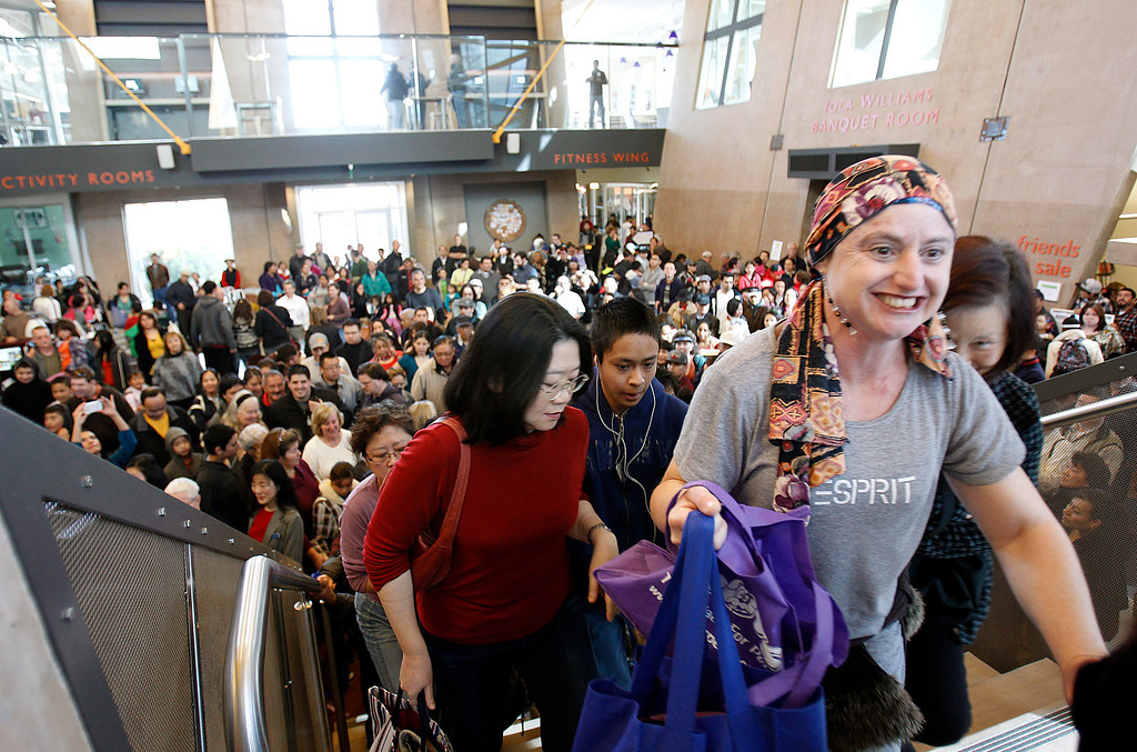 . At right, Stephanie Kleinman joins the crowd of people heading into the library after the grand opening celebration at the Seven Trees Branch Library, in San Jose, Calif. on Saturday, January 26, 2013.   (LiPo Ching/Staff)