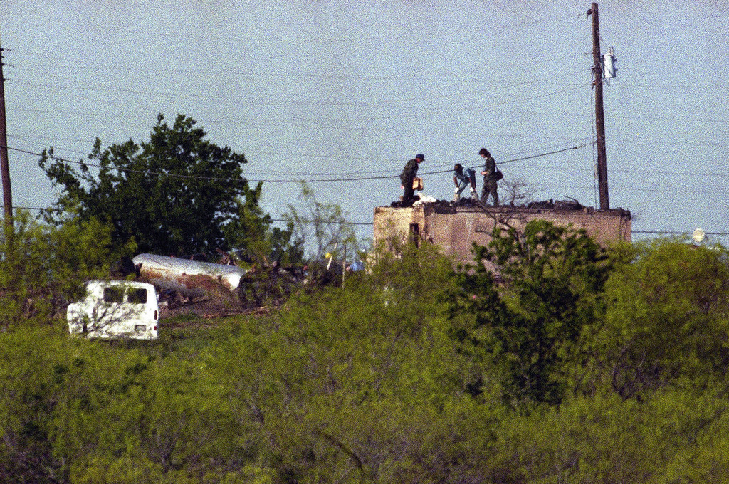 . Investigators look over the remains of victims piled on the roof of a bunker which remains from the destroyed Branch Davidian compound near Waco, Texas on April 22, 1993. (AP Photo/Ron Heflin)