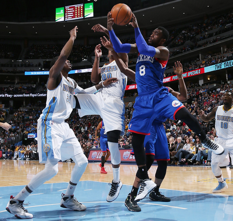 . Philadelphia 76ers guard Troy Wroten, right, drives for shot as Denver Nuggets forwards Darrell Arthur, left, and Quincy Miller defend during the first quarter of an NBA basketball game in Denver on Wednesday, Jan. 1, 2014. (AP Photo/David Zalubowski)