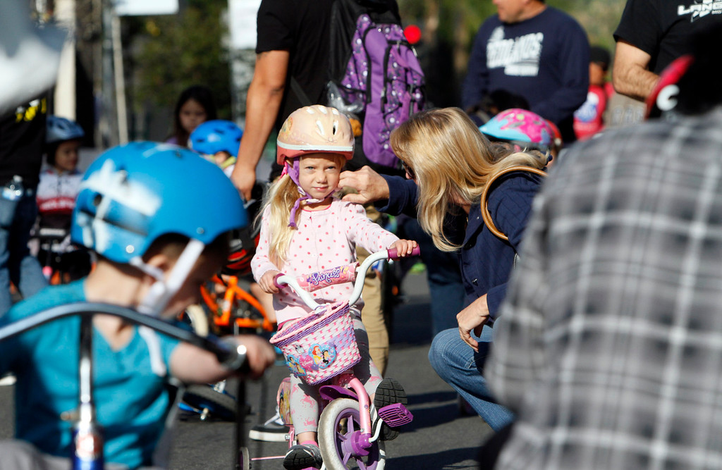 . A rider has her helmet adjusted before the start of the public race portion of the Redlands Bicycle Classic on Saturday, April 5, 2014 in Redlands, Ca. (Photo by Micah Escamilla for the Redlands Daily Facts)