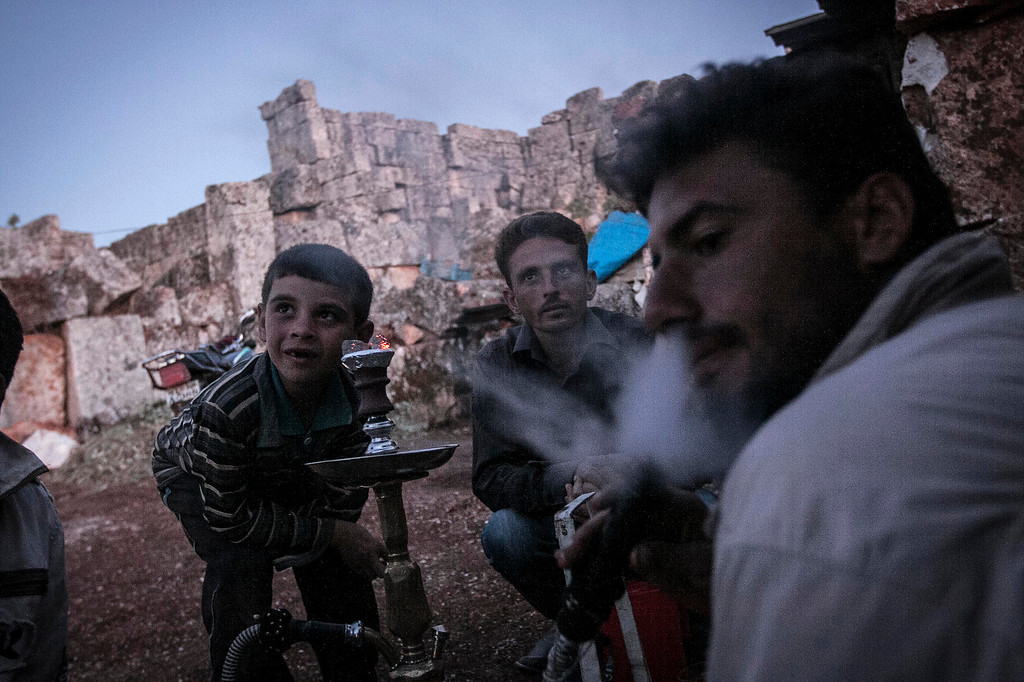 . In this Friday, Sept. 27, 2013 photo, displaced Syrian men and children gather around a water pipe and chat at sunset near Kafer Rouma, in ancient ruins used as temporary shelter by those families who have fled from the heavy fighting and shelling in the Idlib province countryside of Syria. (AP Photo)