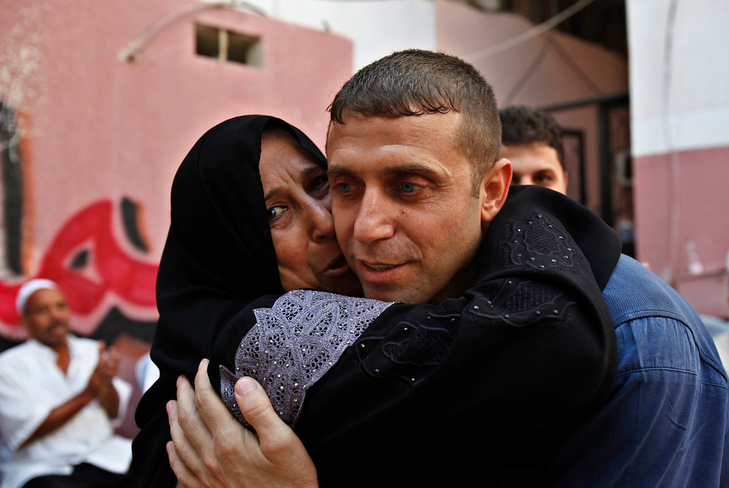 . Released Palestinian prisoner, Nehad Jondiya, hugs his sister Um rami, after 24 years spent at Israeli jail, at his family house in Gaza City, Wednesday, Aug. 14, 2013. Israelis and Palestinians were to hold their first formal peace talks on home turf in the Middle East in nearly five years Wednesday, hours after Israel released 26 long-held Palestinian prisoners who were given a boisterous homecoming by cheering crowds. (AP Photo/Adel Hana)