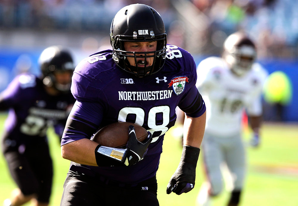 . Northwestern defensive lineman Quentin Williams (88) returns a interception for a touchdown during the first half of the Gator Bowl NCAA college football game against Mississippi State, Tuesday, Jan. 1, 2013, in Jacksonville, Fla. (AP Photo/Stephen Morton)