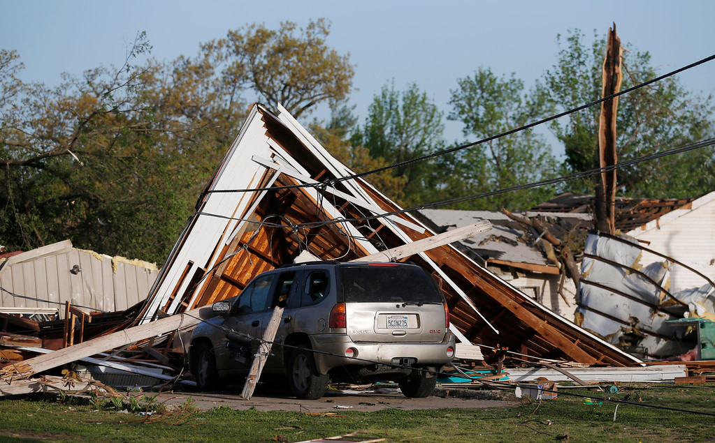 . An SUV is covered by debris from a tornado in Baxter Springs, Kan., Monday, April 28, 2014. Sunday\'s tornado damaged dozens of buildings and injured at least 25 people. (AP Photo/Orlin Wagner)